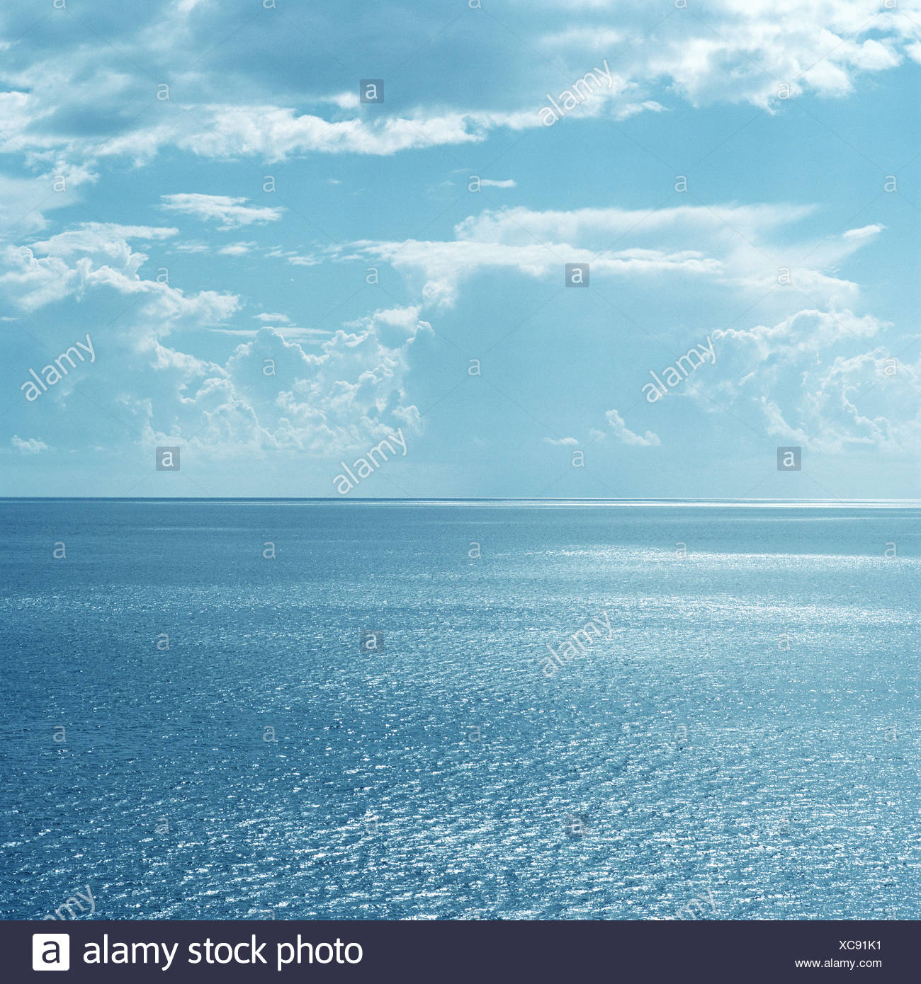 Clouds over still ocean waters Stock Photo