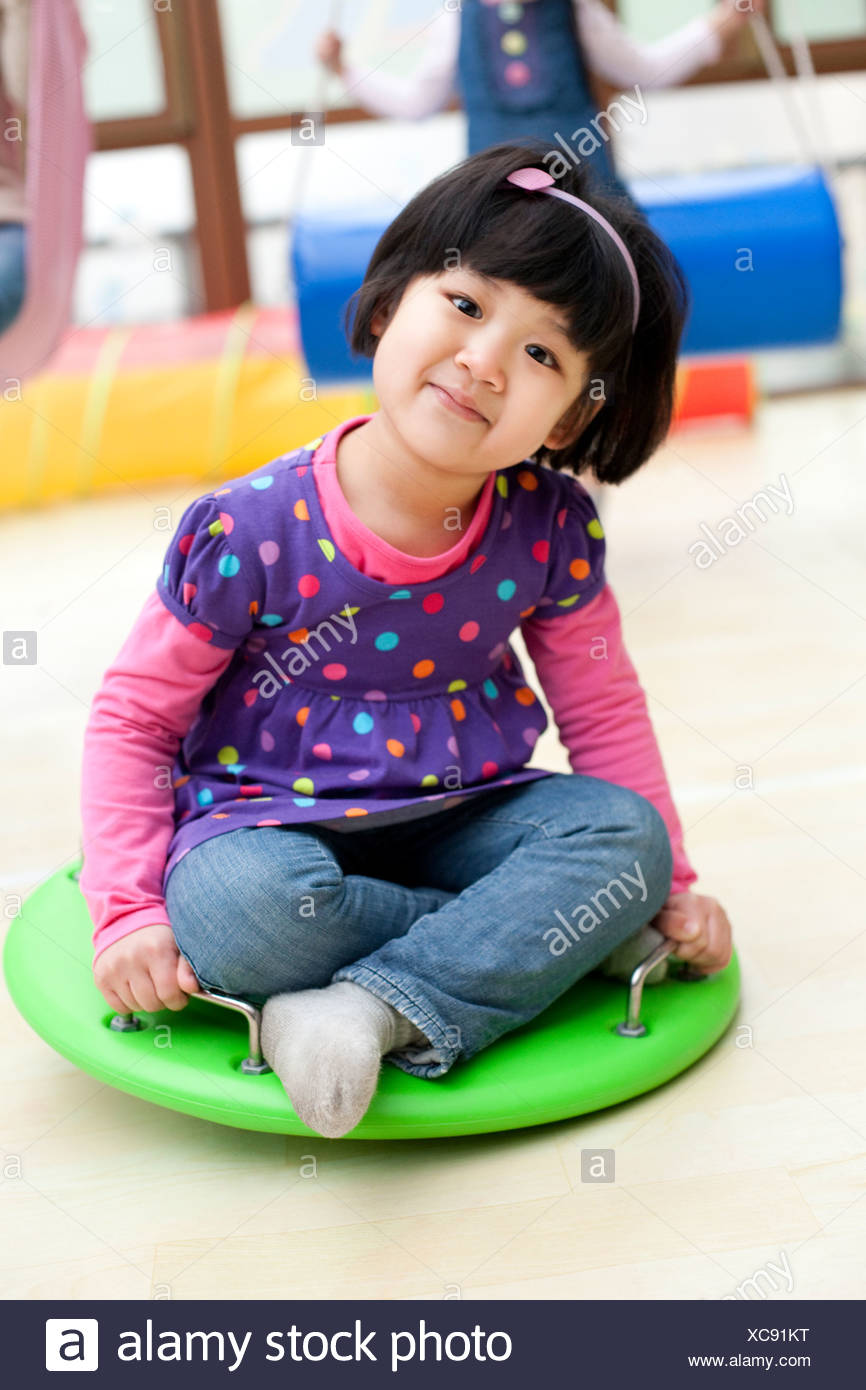 Cute girl sitting on a big toy dreidel in kindergarten - Stock Image