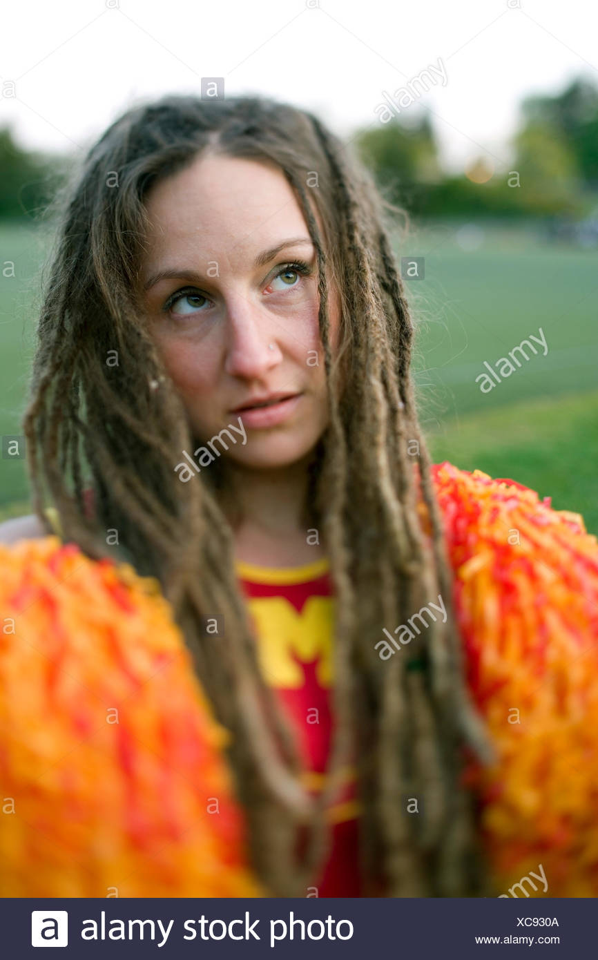 Cheerleader with dreadlocks and pom poms with look of desperation - Stock Image