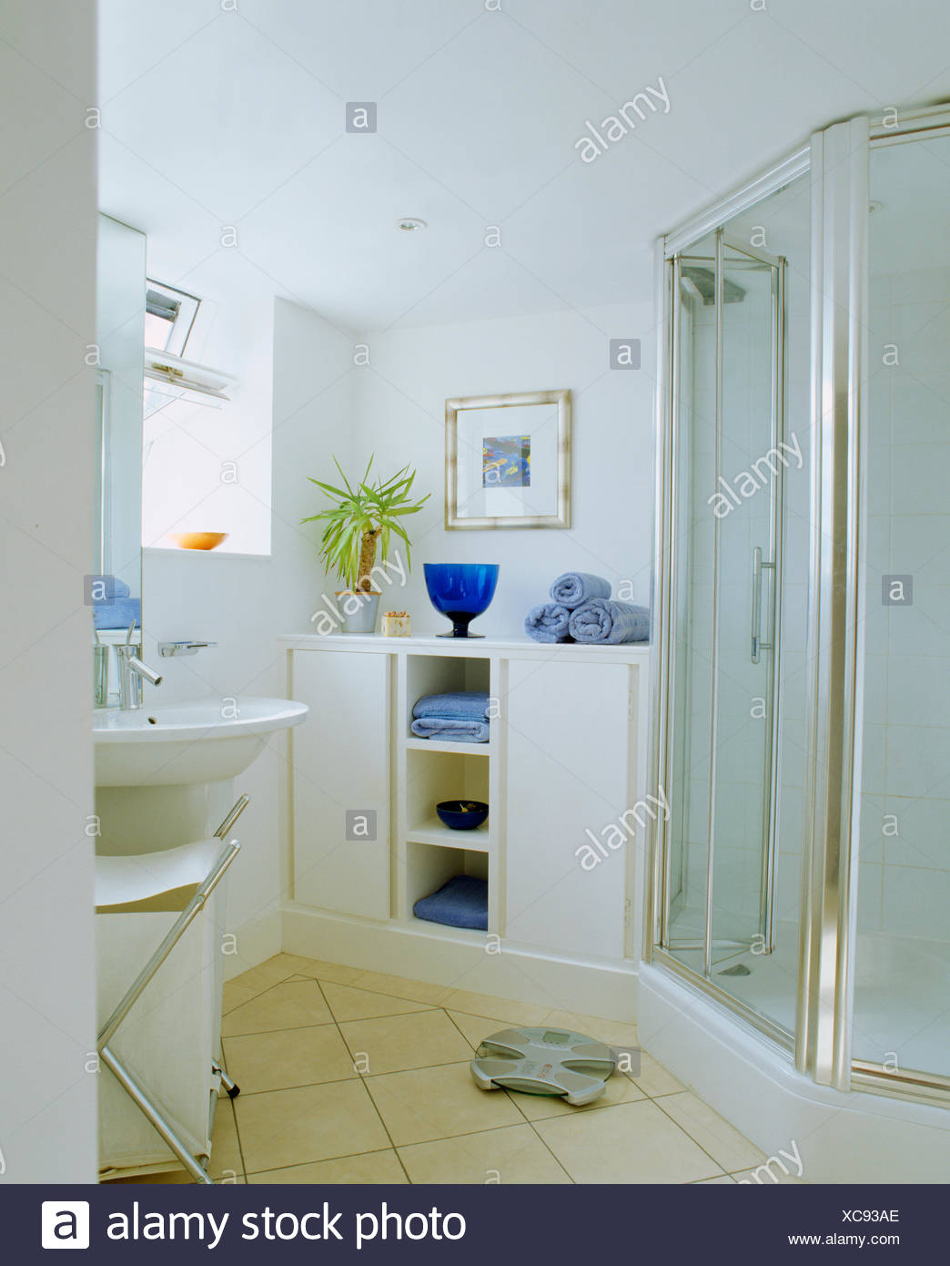 Large blue glass vase and pale blue towels on shelf unit in modern ...