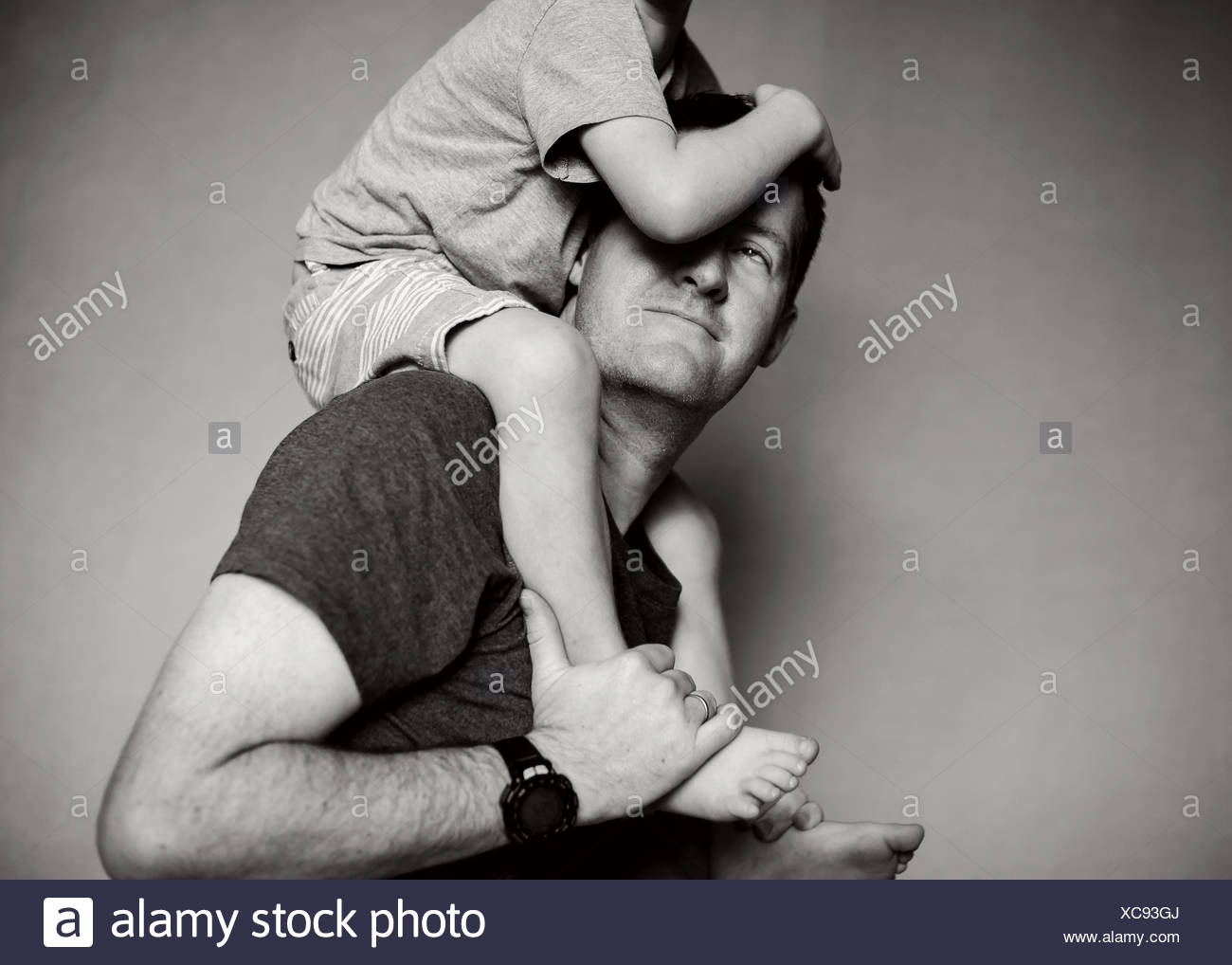 Boy sitting on his father's shoulders Stock Photo