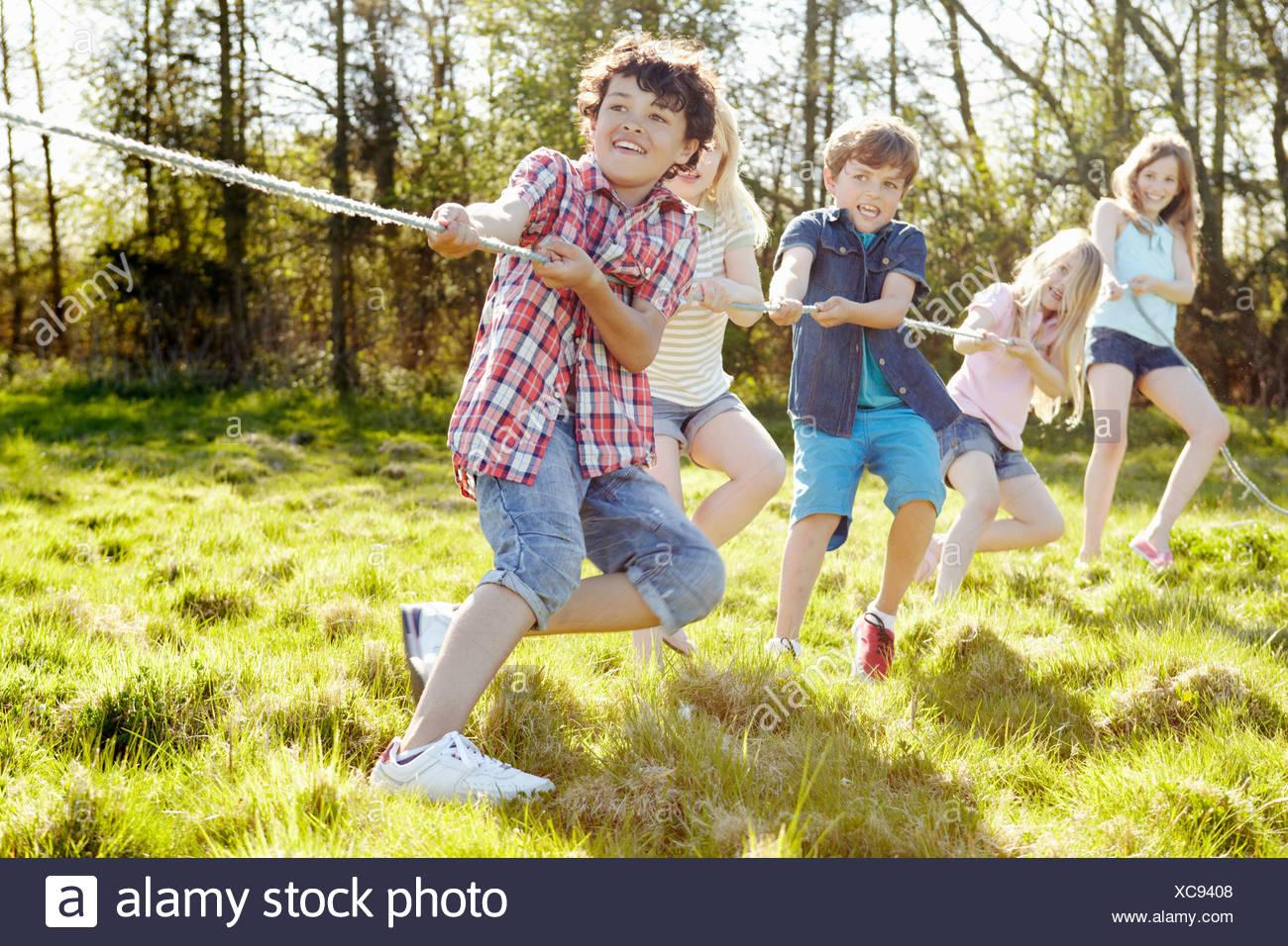 Group of young children playing tug o war - Stock Image