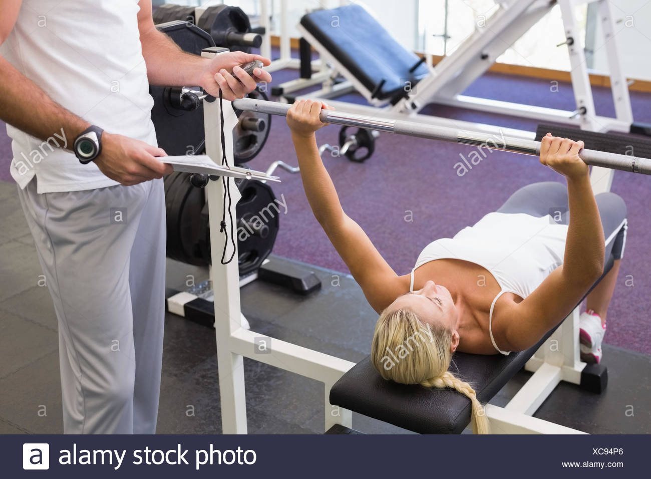 Trainer with clipboard besides woman lifting barbell in gym Stock Photo