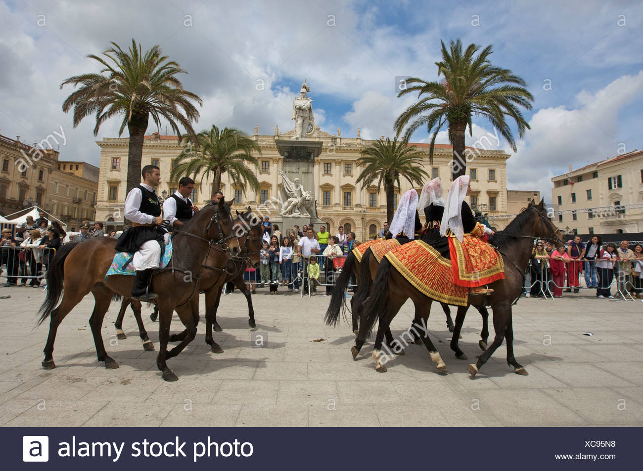 Men and women riding horses while wearing traditional costumes at the Cavalcata Sarda parade on the Piazza Italia in Sassari, S - Stock Image