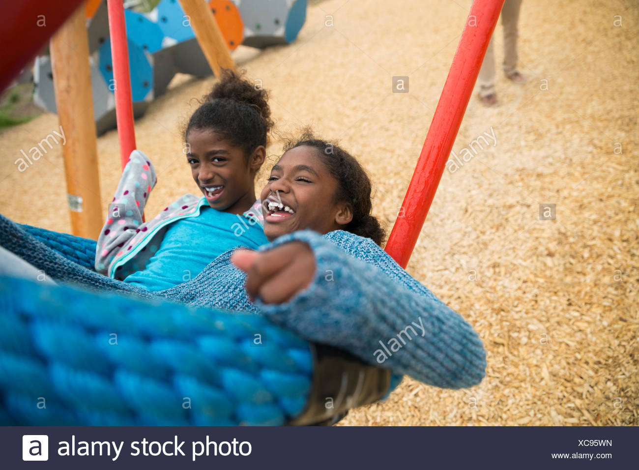 Carefree sisters swinging at playground - Stock Image