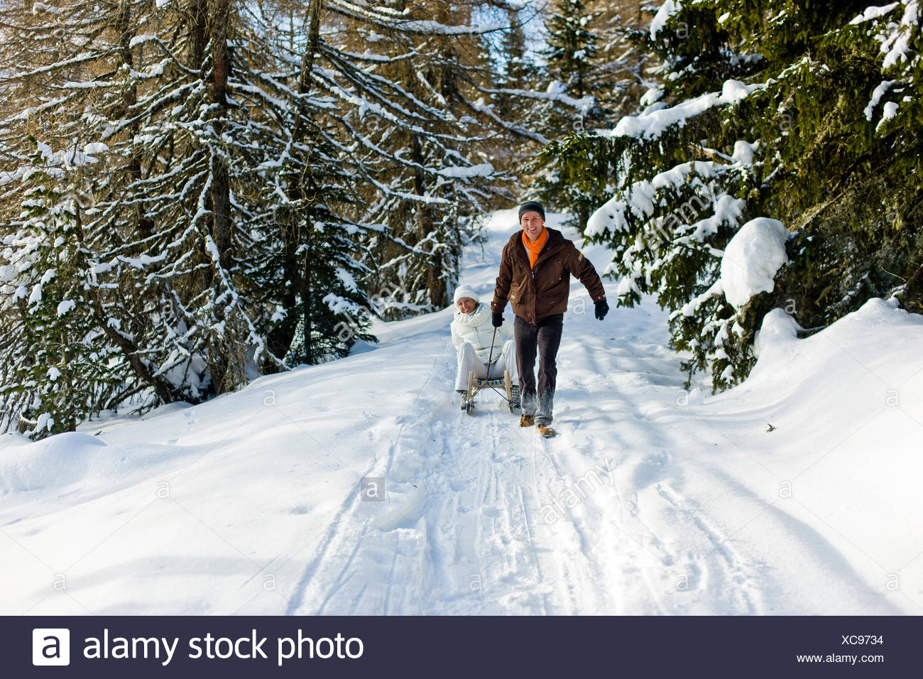 Man pulling a woman sitting on a sledge, Muehlen, Styria, Austria - Stock Image