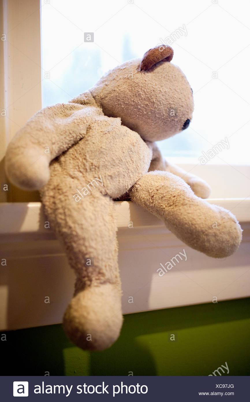 Teddy bear on windowsill - Stock Image
