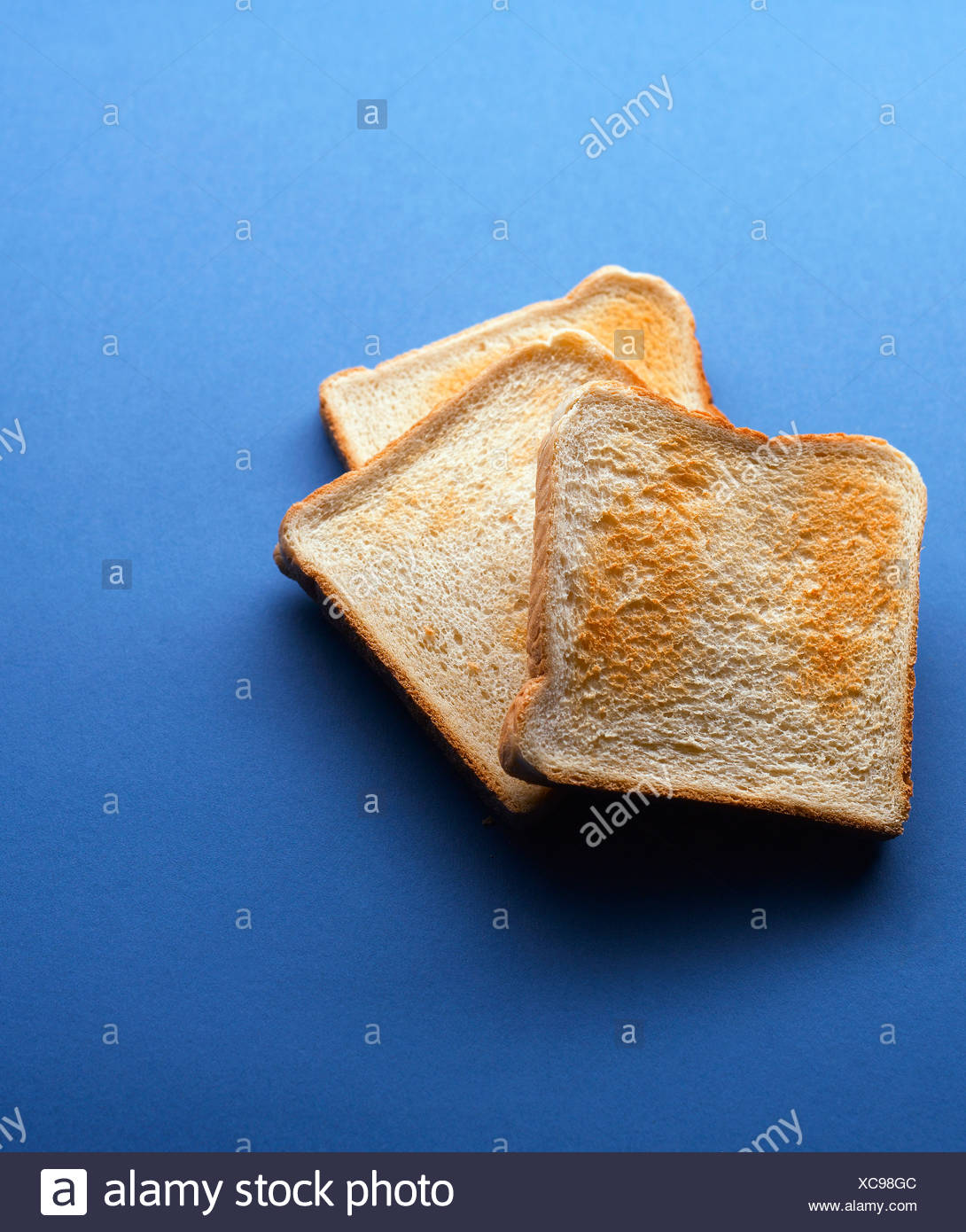 Toasted bread slices on blue background - Stock Image