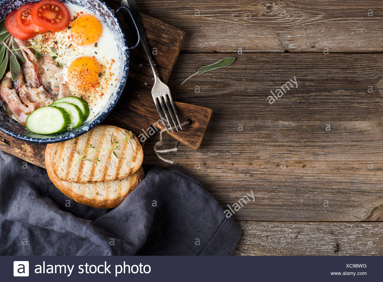 Breakfast set. Pan of fried eggs with bacon, fresh tomato, cucumber, sage and bread on rustic serving board over wooden backgrou - Stock Image