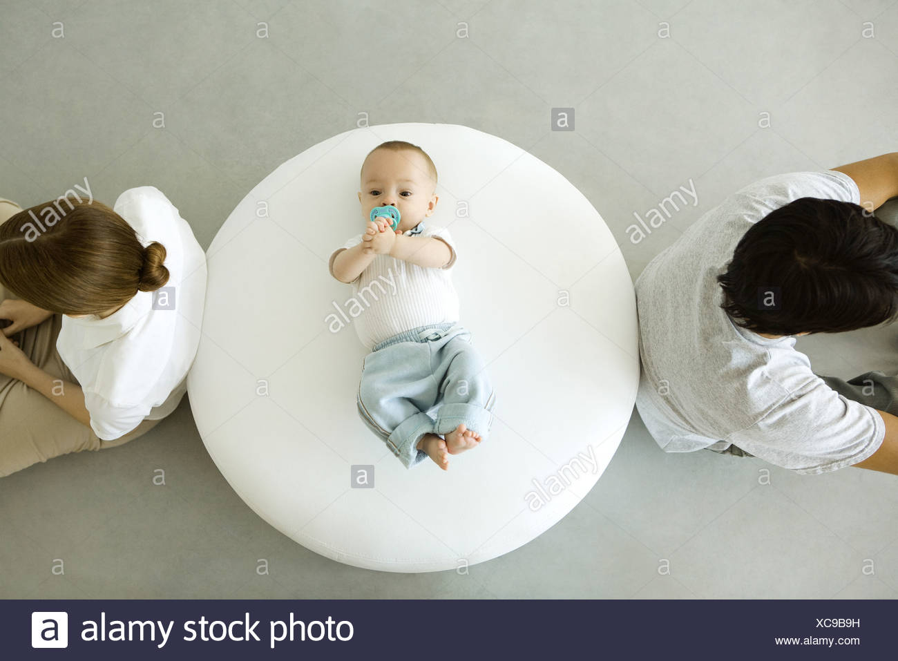 Infant lying on ottoman, mother and father sitting with backs turned, overhead view - Stock Image