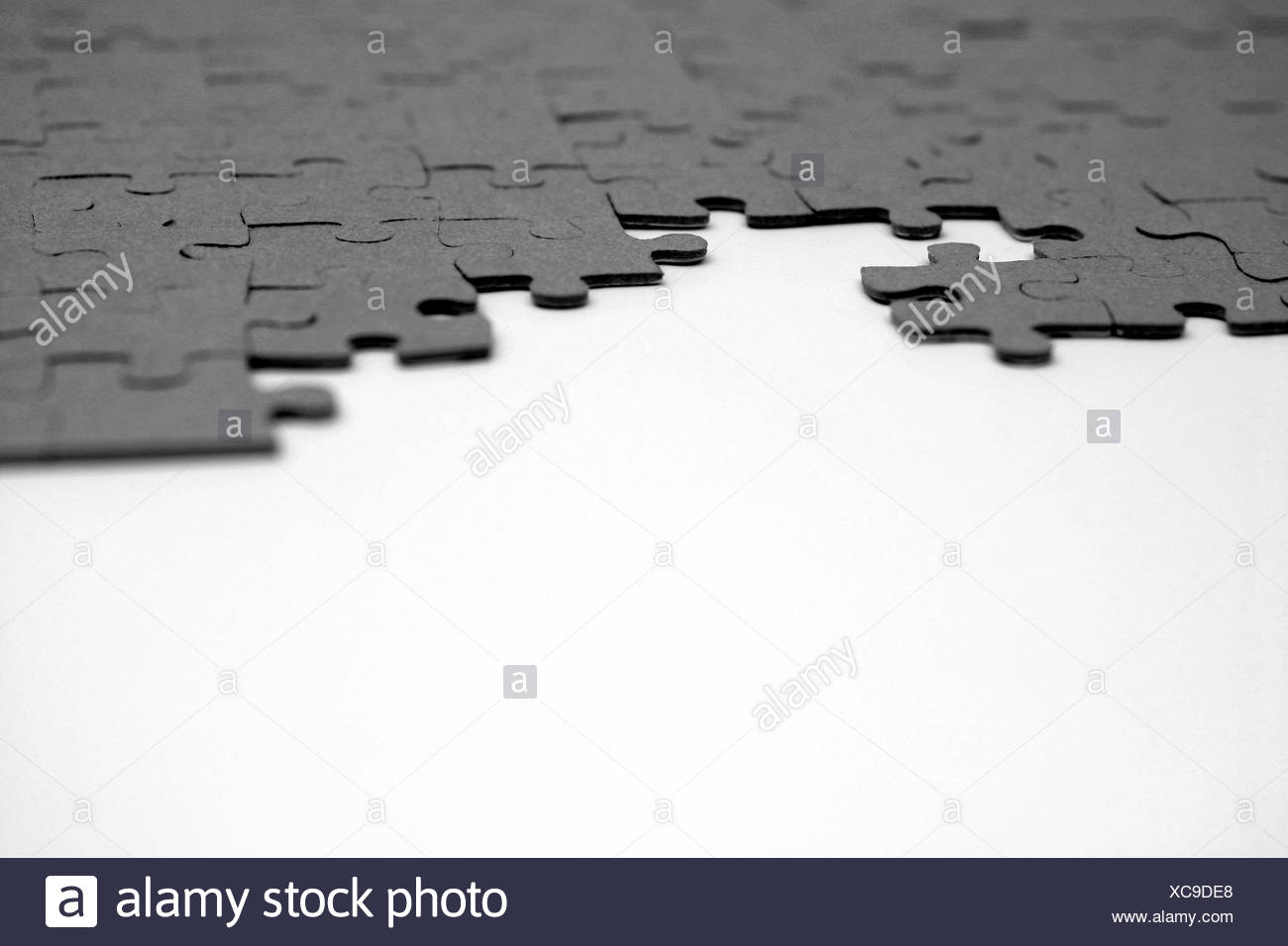 Small pieces of varied shapes of a puzzle are joined together in the slots - Stock Image