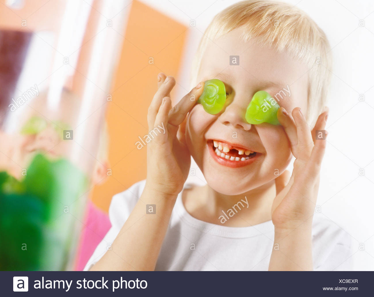 Boy covering his eyes with candies - Stock Image