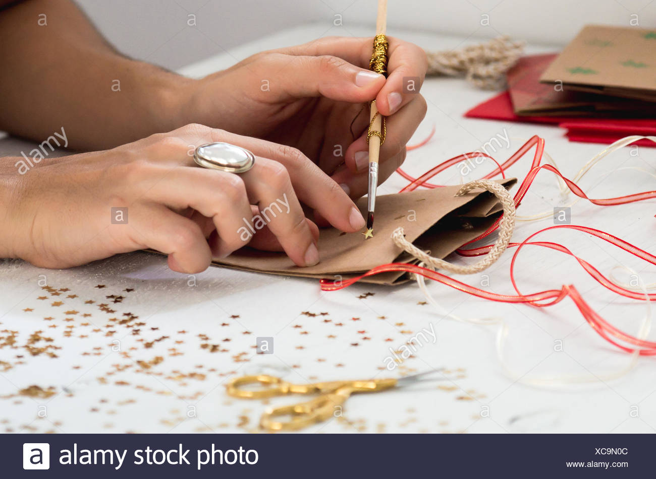 Cropped Image Of Hand Decorating Paper Bag On Table Stock Photo