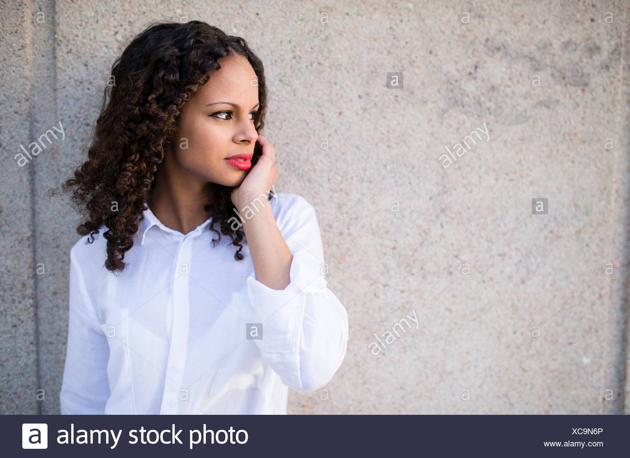 Portrait of young woman with red lips watching something - Stock Image