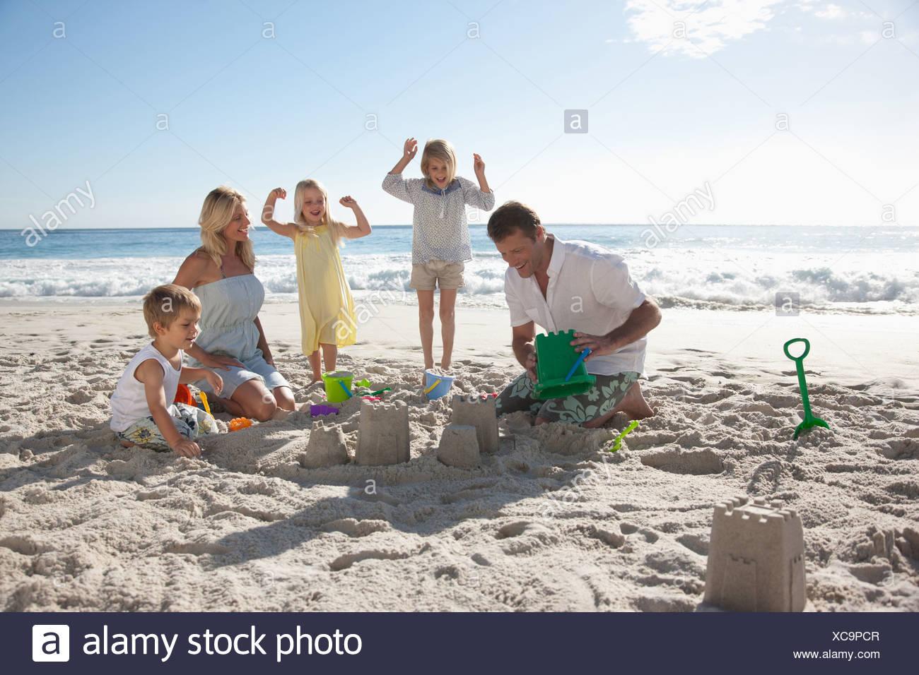 Family making sand castles on beach - Stock Image