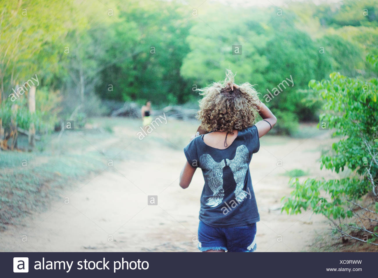 Rear View Of Woman Walking On Pathway - Stock Image