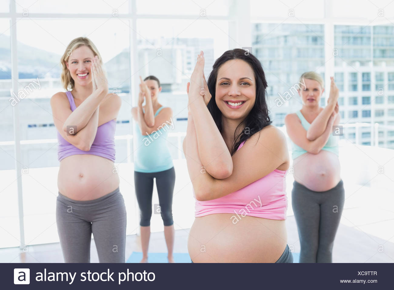 Happy pregnant women in yoga class standing in eagle pose - Stock Image