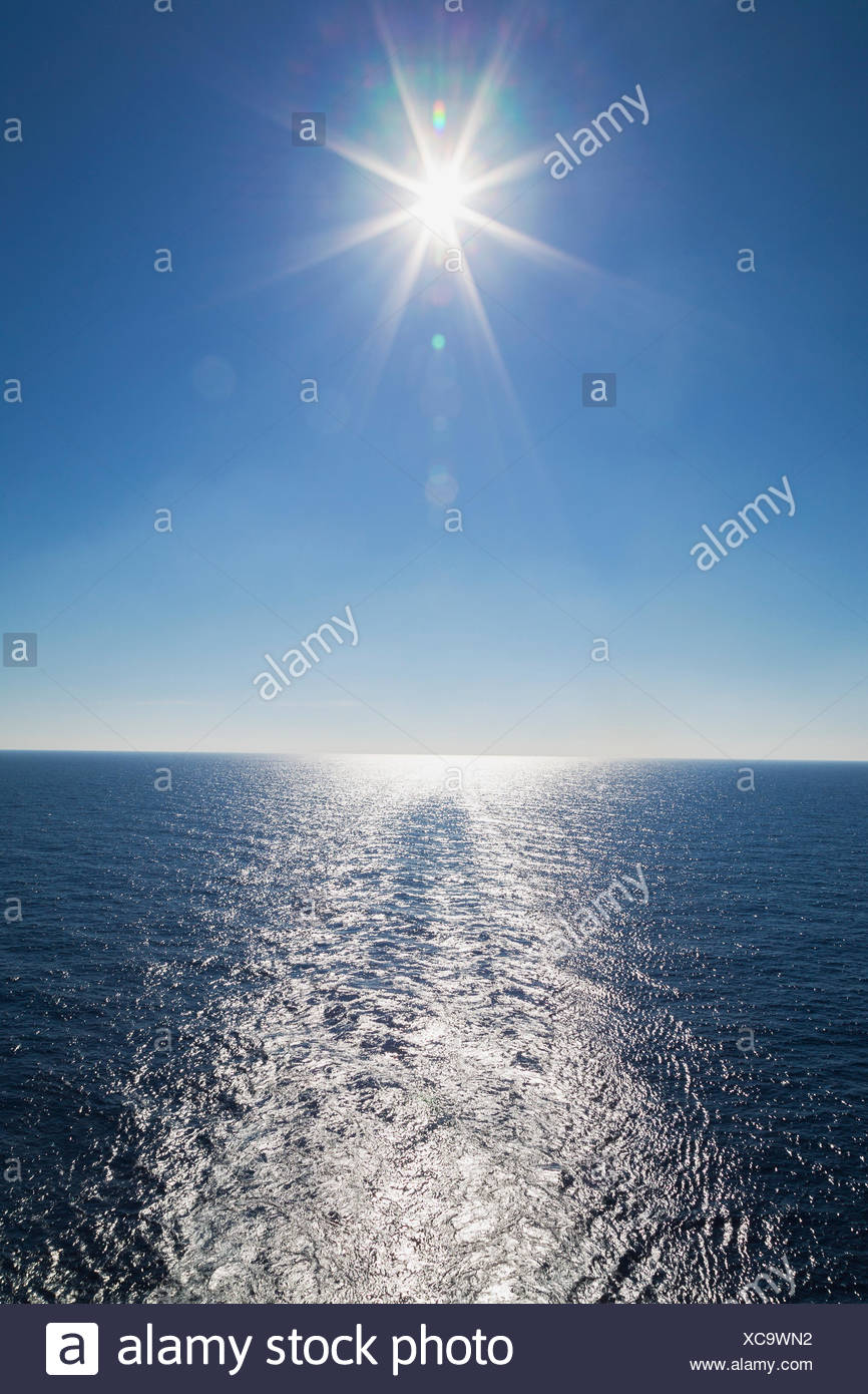 Ship's wake and sunburst over shimmering Mediterranean sea in late afternoon off the coast of Italy - Stock Image