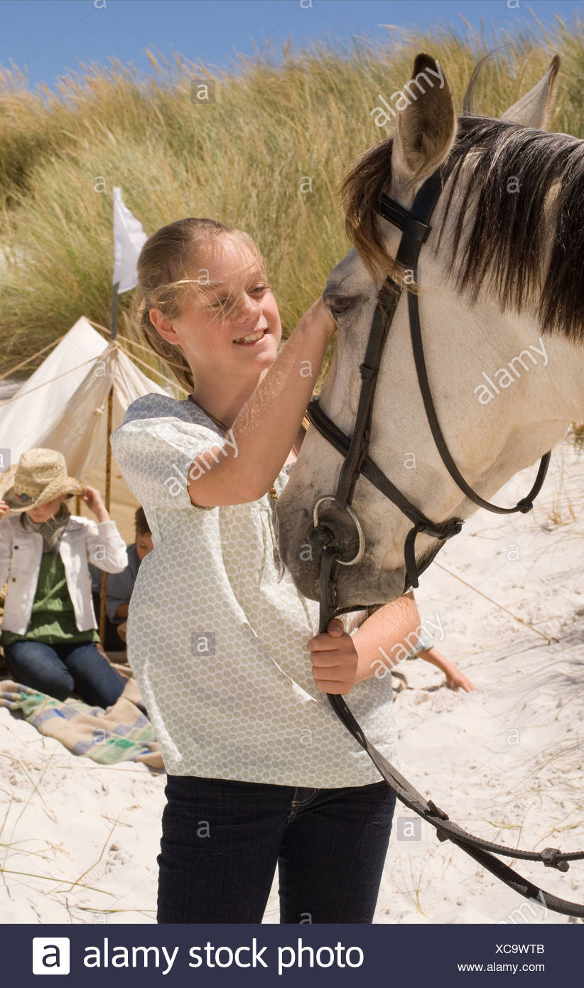 A girl stroking a horse Stock Photo