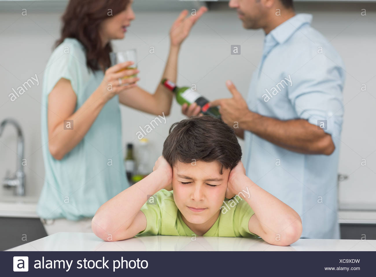 Sad young boy covering ears while parents quarreling - Stock Image