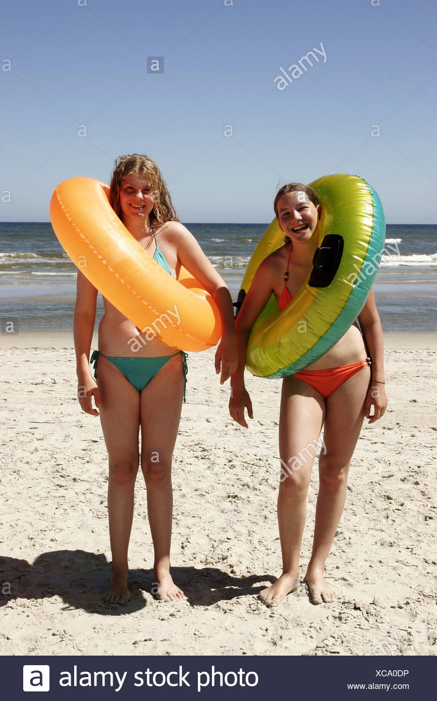 Girls two cheerfully bikini swimming-tires beach stands people teenagers teenagers friends gaze camera fun joy laughter summers - Stock Image