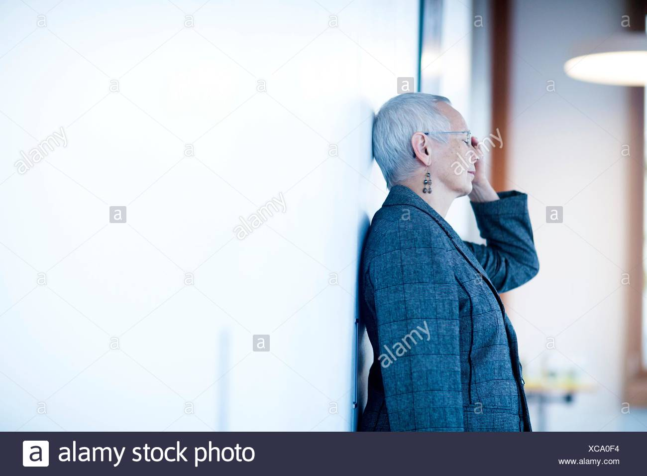Side view of mature woman leaning against wall, hand on head, eyes closed looking stressed - Stock Image