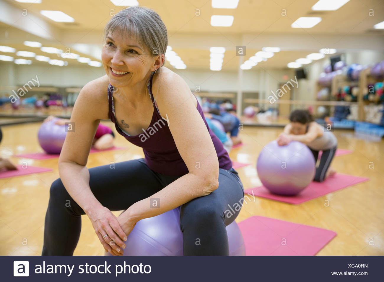 Smiling woman on fitness ball in exercise class - Stock Image
