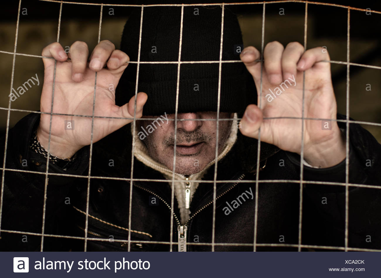 Portrait of a man trapped behind a metal fence - Stock Image