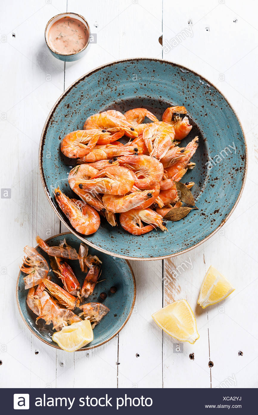 Prepared shrimps on blue plate on wooden background - Stock Image