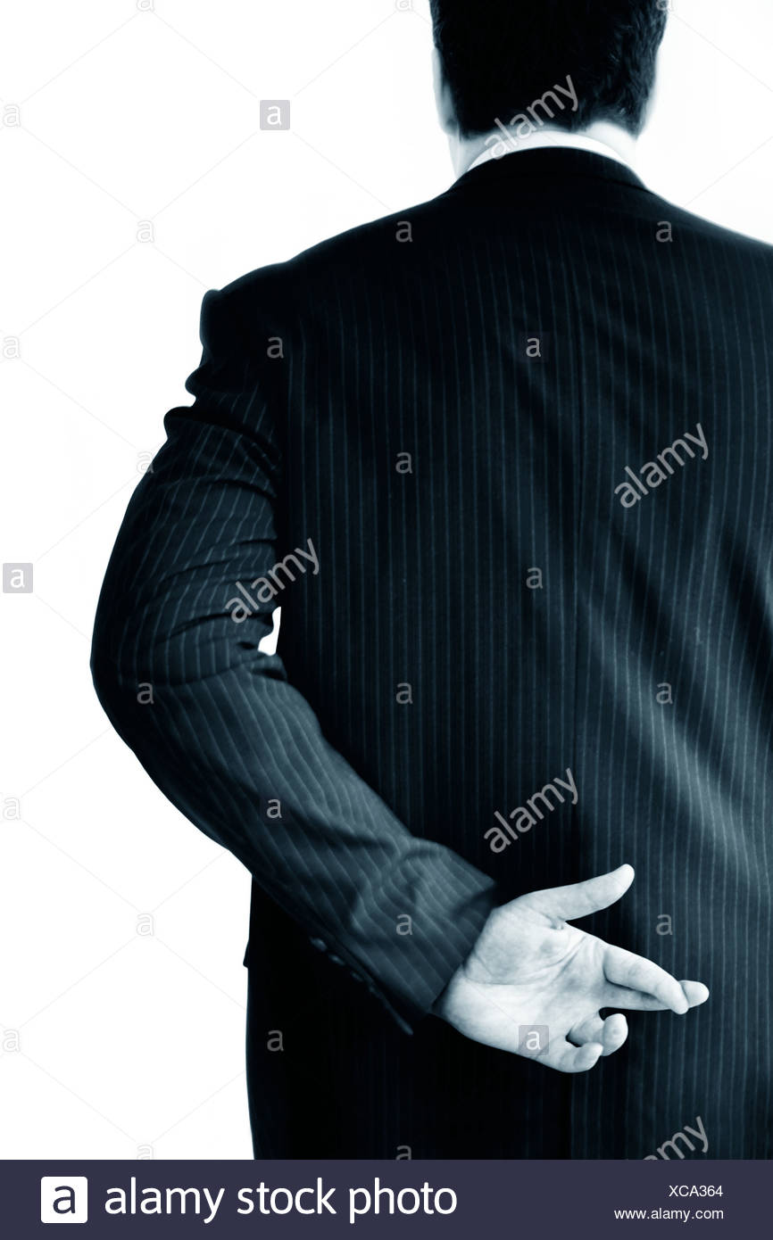 a businessman with his fingers crossed - Stock Image