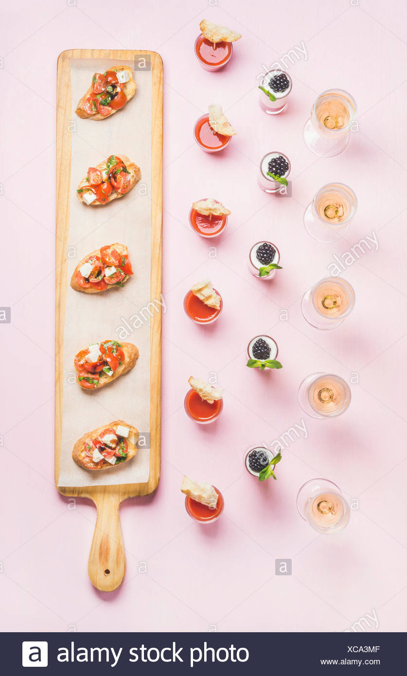 Catering, banquet food concept. Various snacks, brushetta sandwiches, gazpacho shots, desserts with berries on corporate event, christmas, birthday, w Stock Photo