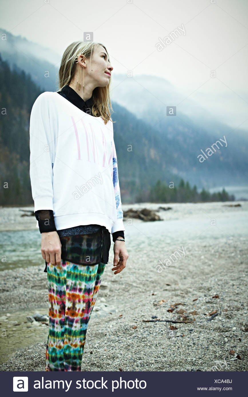 Hippy woman standing in mountains Stock Photo