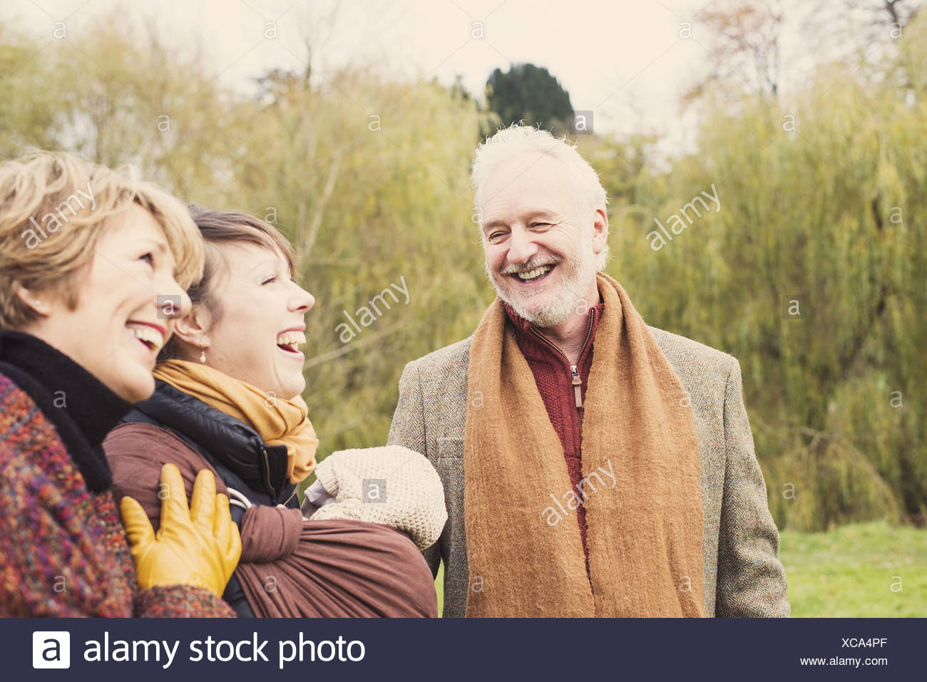 Three generation family laughing - Stock Image
