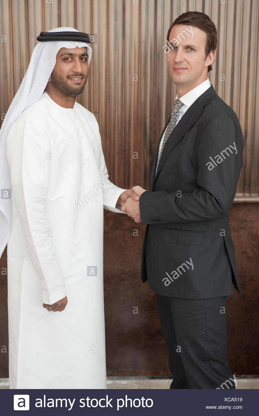 Western and middle eastern businessmen shaking hands - Stock Image