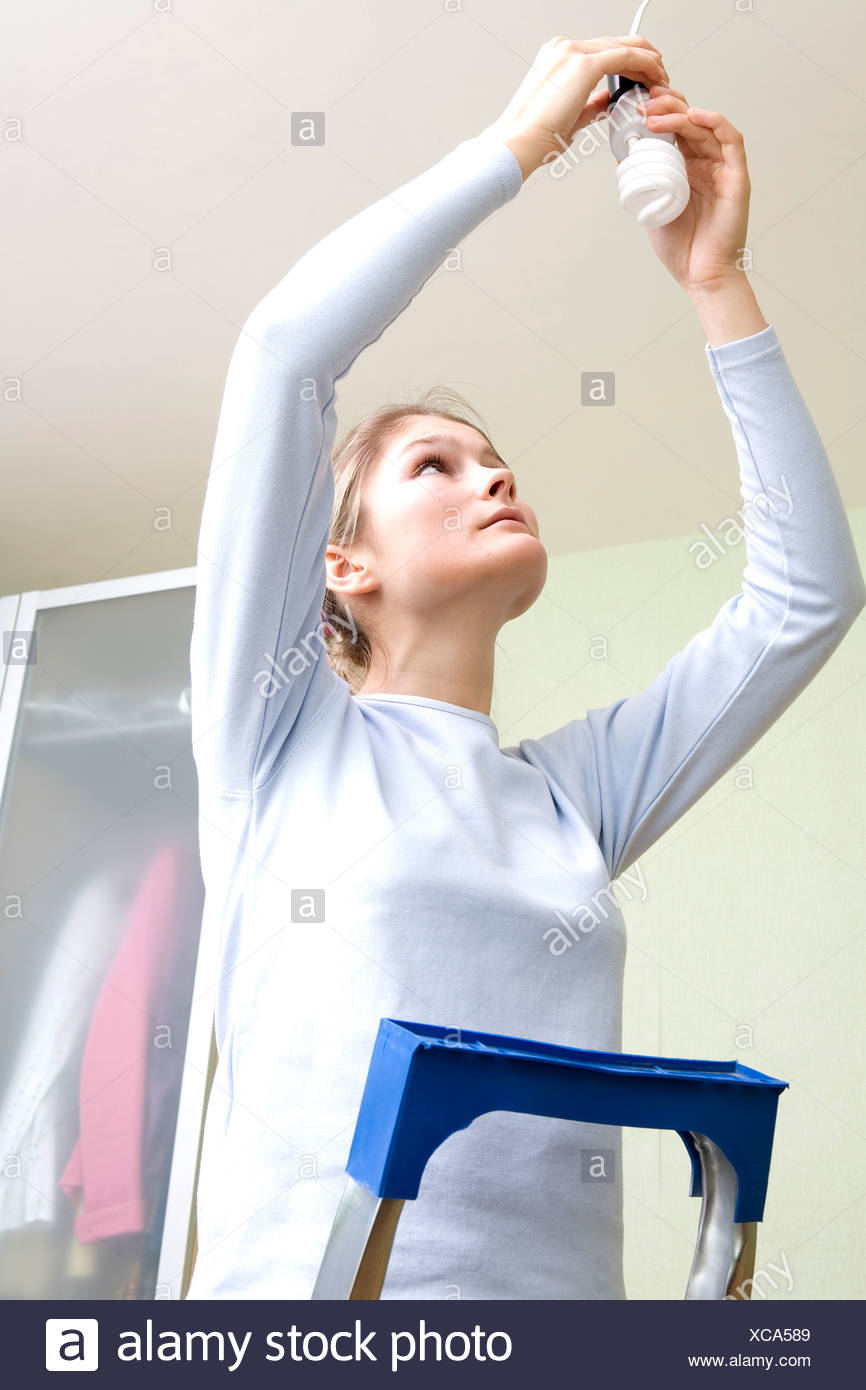 young woman fixing low energy light bulb - Stock Image