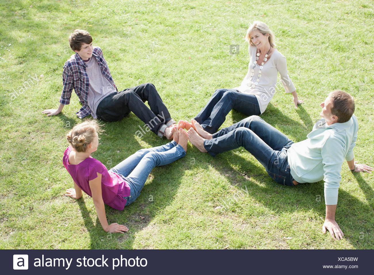 Family sitting on grass - Stock Image