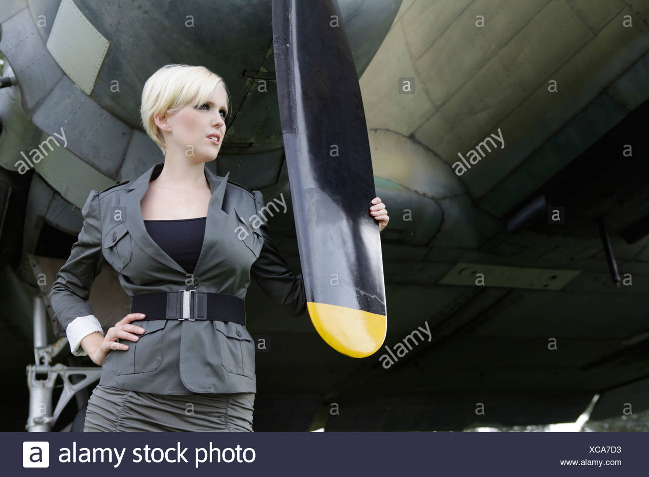 Young woman standing at propeller plane - Stock Image