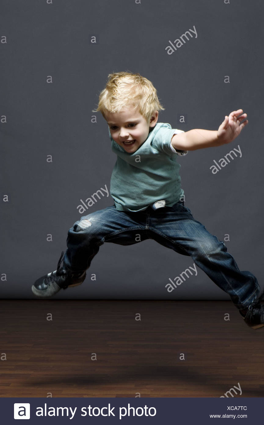 Child, boy, 5 years, jump, play, high-spirited, studio recording, childhood, lighthearted, blond, jeans, T-shirt, romp, rave, melted, motion, actively, activity, fun, joy, amusement, inside, whole body recording, Stock Photo