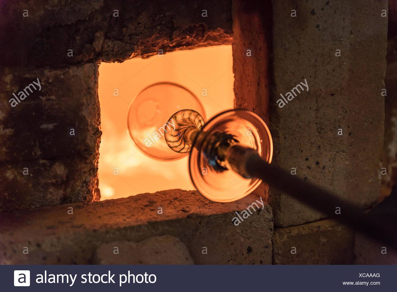 Glassblower heating glass in furnace - Stock Image