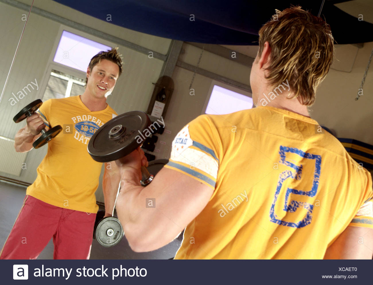 Young, beefy man trains with dumbbells - Stock Image