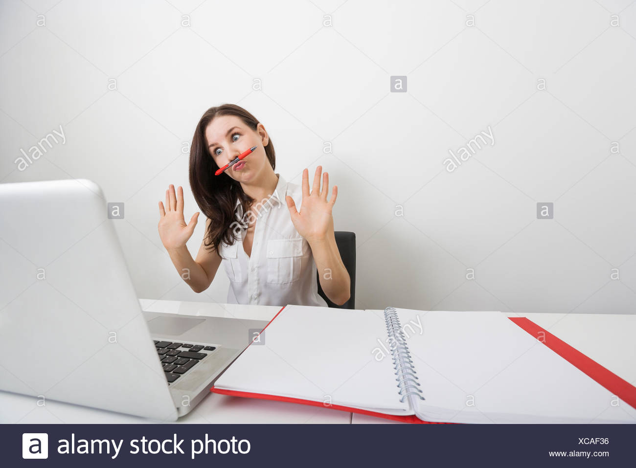 Astonished businesswoman looking at laptop while holding pen under nose in office - Stock Image