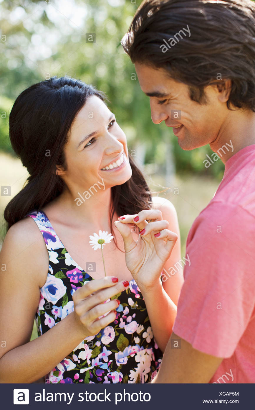 Smiling couple plucking petals from daisy Stock Photo