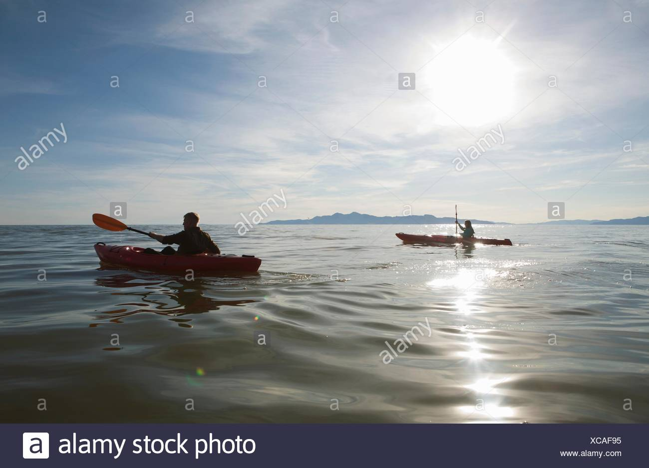 Couple kayaking, sunlight reflecting on water, Great Salt Lake, Utah, USA - Stock Image