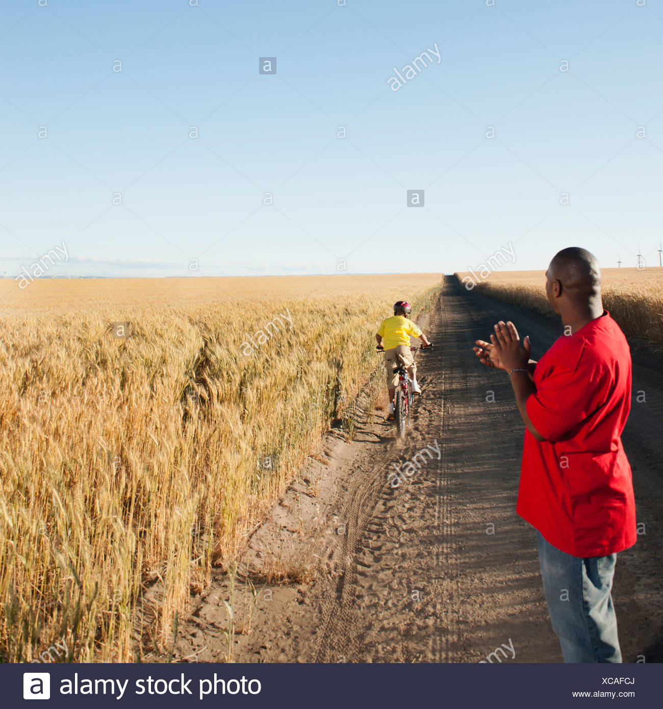 USA, Oregon, Wasco, Father clapping as son is cycling along dirt road in fields - Stock Image