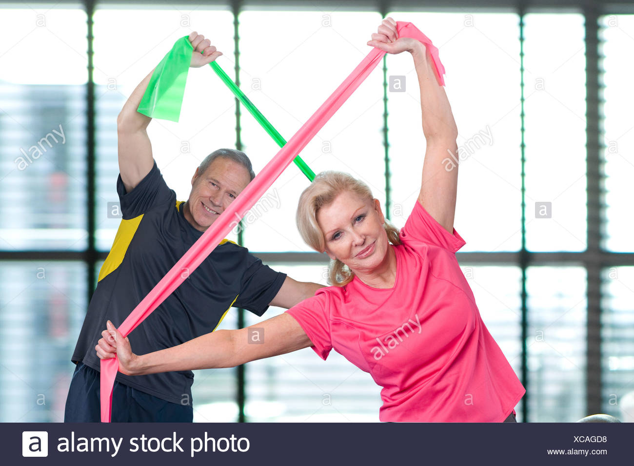 Portrait of couple stretching with resistance bands overhead - Stock Image
