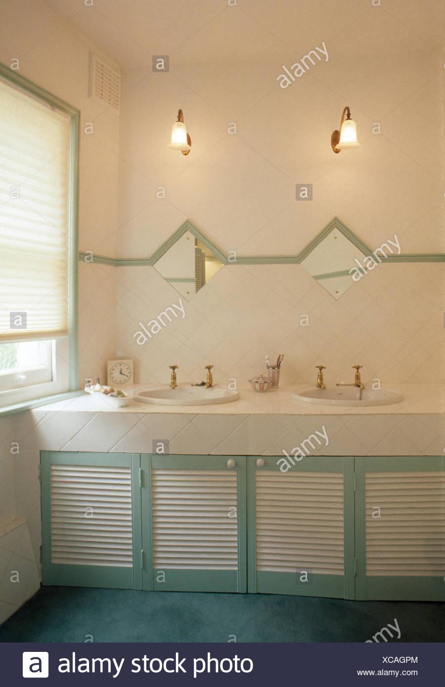 louvre doors on vanity unit with double basins in seventies bathroom stock image
