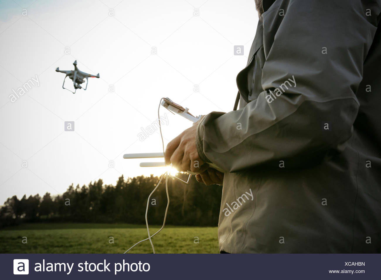Man on a meadow flying drone Stock Photo