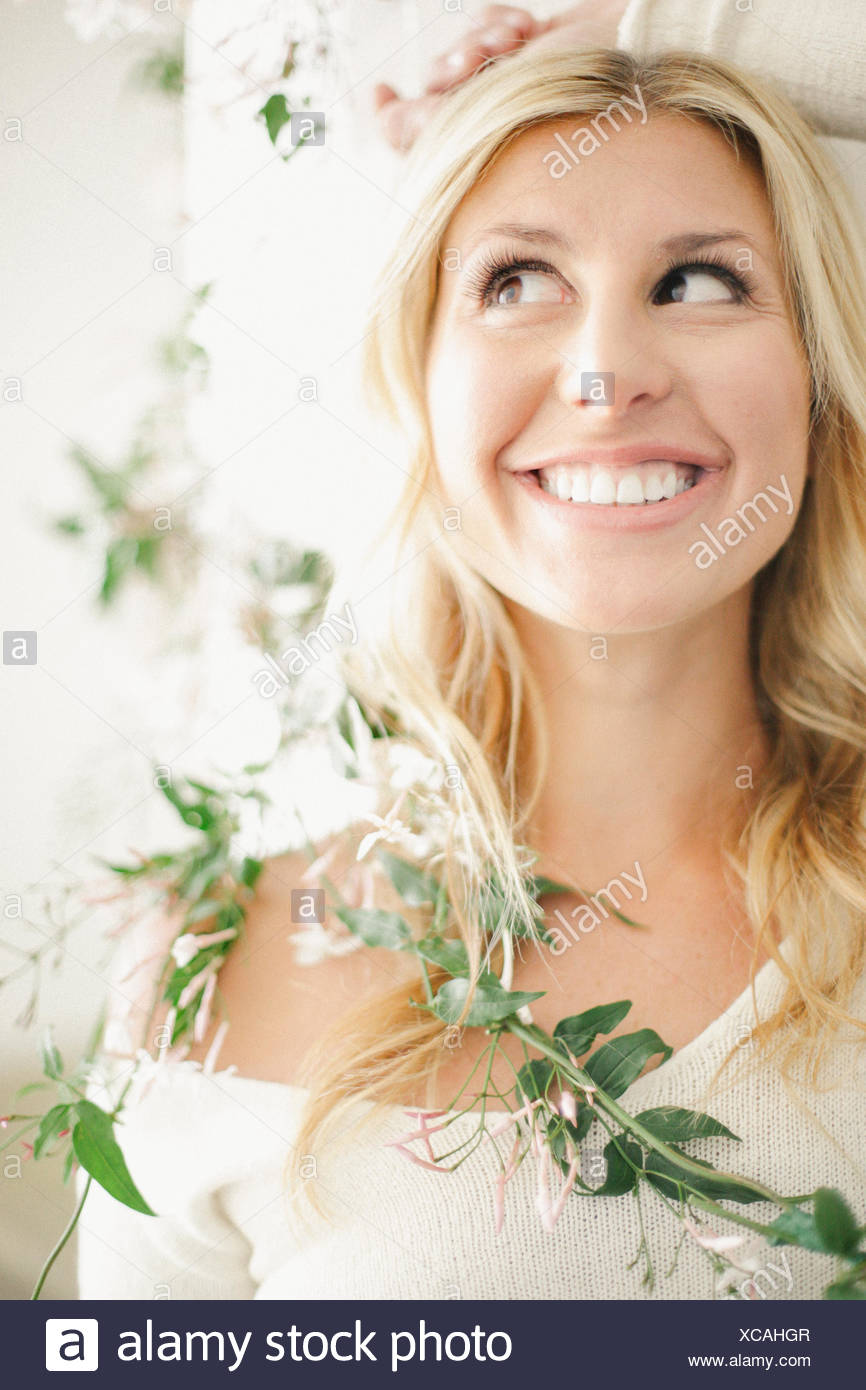 A blonde woman smiling lying down with a leafy garland wound around her neck and torso. - Stock Image