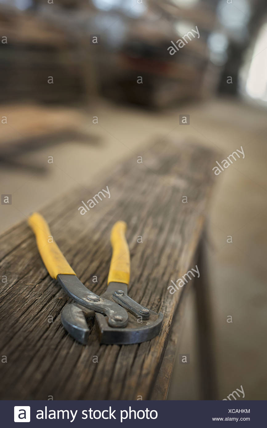 A heap of recycled reclaimed timber planks of wood in a timber yard A pair of pliers on a plank of wood - Stock Image
