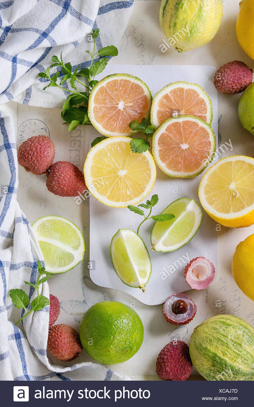 Variety of whole and sliced citrus fruits pink tiger lemon, lemon, lime, mint and exotic lichee on white chopping board with kitchen towel over white  Stock Photo